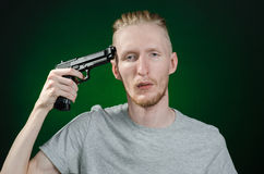 Firearms and murderer topic: suicide in a gray t-shirt holding a gun on a dark green background  in studio Stock Photos