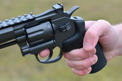 Firearms and security topic: hand man with a gun ready to shoot. Outside. Selective focus Stock Images