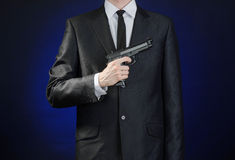Firearms and security topic: a man in a black suit holding a gun on a dark blue background in studio  Royalty Free Stock Image