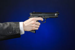 Firearms and security topic: a man in a black suit holding a gun on a dark blue background in studio  Stock Photo