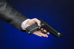Firearms and security topic: a man in a black suit holding a gun on a dark blue background in studio  Stock Images