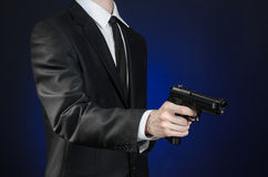 Firearms and security topic: a man in a black suit holding a gun on a dark blue background in studio isolated Stock Images