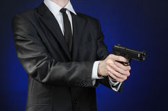 Firearms and security topic: a man in a black suit holding a gun on a dark blue background in studio isolated Stock Image
