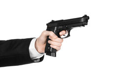 Firearms and security topic: a man in a black suit holding a gun on an isolated white background in studio Stock Photo
