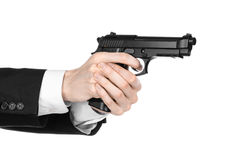 Firearms and security topic: a man in a black suit holding a gun on an isolated white background in studio Stock Images