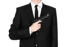 Firearms and security topic: a man in a black suit holding a gun on an isolated white background in studio. Firearms and security topic: a man in a black suit Royalty Free Stock Photo