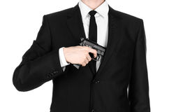 Firearms and security topic: a man in a black suit holding a gun on an isolated white background in studio. Firearms and security topic: a man in a black suit Royalty Free Stock Photos