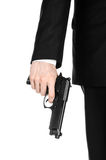 Firearms and security topic: a man in a black suit holding a gun on an isolated white background in studio. Firearms and security topic: a man in a black suit Stock Photography