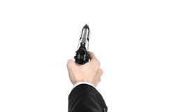 Firearms and security topic: a man in a black suit holding a gun on an isolated white background in studio Royalty Free Stock Photos