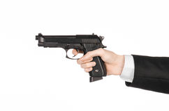 Firearms and security topic: a man in a black suit holding a gun on an  white background in studio Royalty Free Stock Image