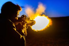 Fireball While shooting a rifle. Flames shooting out of the end of an AR-15 assault rifle while shooting at a range royalty free stock image