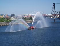 Fireboat Rainbow. A fireboat spouting water on the river with a rainbow included Royalty Free Stock Image