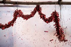 Firecrackers. Hung midair on long fused string during Chinese New Year celebration, ignited  will let out deafening explosion in belief to drive away evil stock image