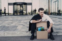 Fired businessman sitting on street. Fired business men sitting frustrated and upset on the street near office building with box of his belongings. He lost work Stock Image