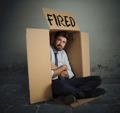 Fired businessman. Desperate and fired businessman hides in the cardboard Royalty Free Stock Photos