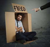Fired businessman. Desperate and fired businessman hides in the cardboard Royalty Free Stock Photography