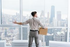 Fired businessman felling sad and carrying his belongings. Great view on the city. Pleasant professional office worker standing with his belongings in the office Royalty Free Stock Photos