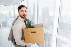 Fired businessman felling sad and carrying his belongings. New period of life. Pleasant skillful employee holding box with his belongings and experincing first Stock Photography