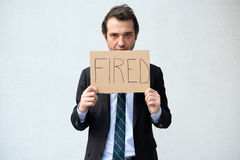 Fired businessman hiding his face with layoff message Royalty Free Stock Photography