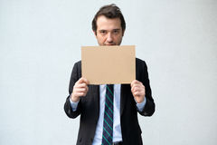 Fired businessman hiding his face with message Stock Photography