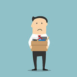 Fired businessman leaving office with box. Disappointed jobless cartoon businessman is carrying a cardboard box with personal belongings, leaving office after Stock Images