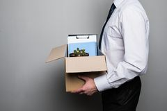 Cropped shot of fired businessman packing office supplies in cardboard box at workplace. Fired businessman packing office supplies in cardboard box at workplace Royalty Free Stock Photo