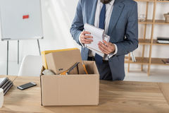 Fired businessman packing office supplies in cardboard box at workplace. Cropped shot of fired businessman packing office supplies in cardboard box at workplace Stock Photography