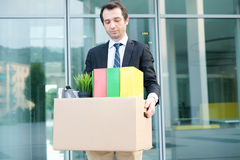 Fired businessman taking away his belongings. Sad fired businessman taking away his belongings from the financial district Stock Photos