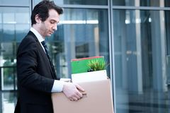 Fired businessman taking away his belongings in wall street Royalty Free Stock Photos