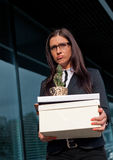 Fired businesswoman holding a box of her belonging Stock Photo