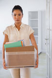 Fired businesswoman holding box of her things Stock Photo