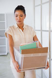 Fired businesswoman holding box of her things Royalty Free Stock Photography