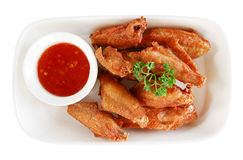 Fired chicken wings with sauce in ceramic plate top view isolated on white background, path Stock Photography