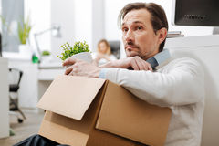 Fired depressed man sitting on the floor in the office stock photography