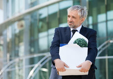 Fired. Depressed senior man in formalwear holding box with his work stuff and looking away Royalty Free Stock Image