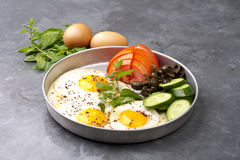 Fired eggs presentation with mints, tomato, olive, cucumber and sumac Stock Images