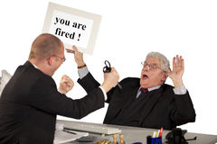 Fired employee attacking senior manager. A fired employee attacking his boss, a senior manager, with a pair of scissors Royalty Free Stock Photography