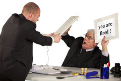 Fired employee attacking senior manager. A fired employee attacking his boss, a senior manager, with a keyboard Royalty Free Stock Photography