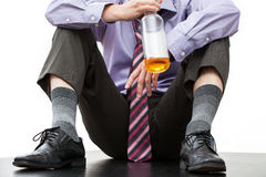 Fired employee with a bottle of rum. Fired employee of corporation drinking a rum on the floor Stock Image