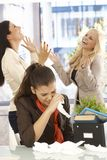 Fired employee crying at desk. Fired female employee crying at desk, colleagues celebrating at the background Royalty Free Stock Image