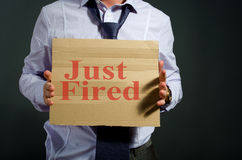 Fired employee. Holding just fired sign in hand Royalty Free Stock Images