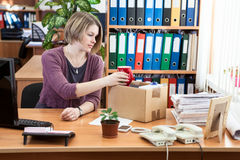 Fired female collecting things in cardboard box. Fired woman collecting things in cardboard box in the workplace Stock Photography