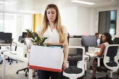 Fired female employee holding box of belongings in an office stock image