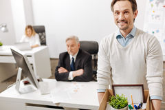 Fired positive employee carrying the box and quitting the job. Never give up. Fired smiling positive employee standing and carrying the box with his personal Stock Photo