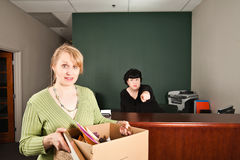 Fired Worker. A female boss points and snears in the background telling a fired worker to get out of the office.  the fired worker looks on in astonishment with Stock Images