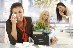 Fired office worker crying at office. Fired young female office worker sitting at desk, crying, colleagues laughing at her at the background Royalty Free Stock Images