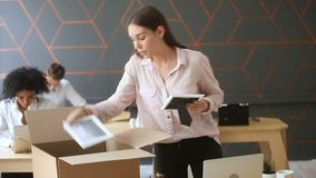 Fired young upset woman packing box standing near work desk. Fired young sad woman packing box standing near work desk, taking all her belongings after being stock footage