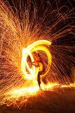 Firedancer surrounded by fire and sparks. A spectacular fire dancer surrounded by streaks of sparks and fire stock photo