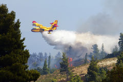 Firefghter water bomber airplane dumping its load Royalty Free Stock Image
