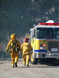 Firefghters and truck. Firefighters walking to a fire truck with smoke in the background Royalty Free Stock Photography